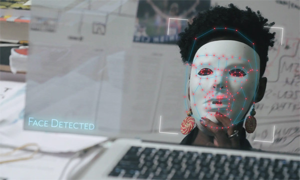 "A Black woman holds a white mask in front of her face, facing a laptop and interactive mirror. Overlaid computer graphics map the facial geometry of the mask, and ""Face Detected"" appears as text in the bottom left-hand corner of the mirror."