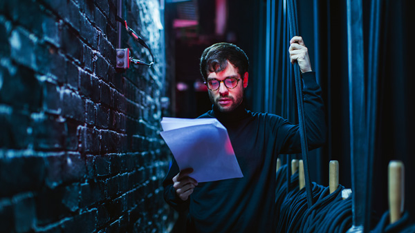 Actor backstage intently reading lines from the script