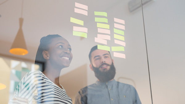 A pair of students smiling as they review ideas on post-it notes stuck to a glass partition