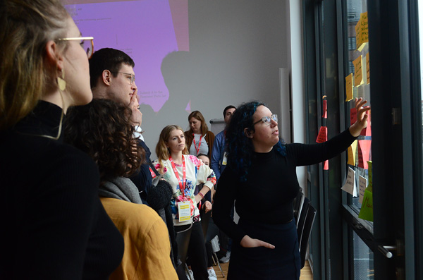 A woman leads a group of people at a Feminist Data Set workshop.