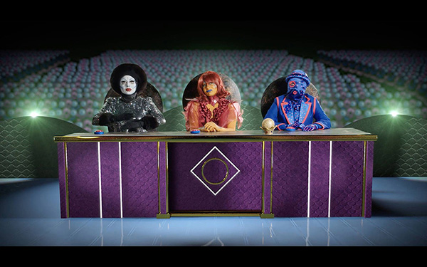 A panel of three elaborately dressed extraterrestrial judges sit behind a large podium inside of a large theatre